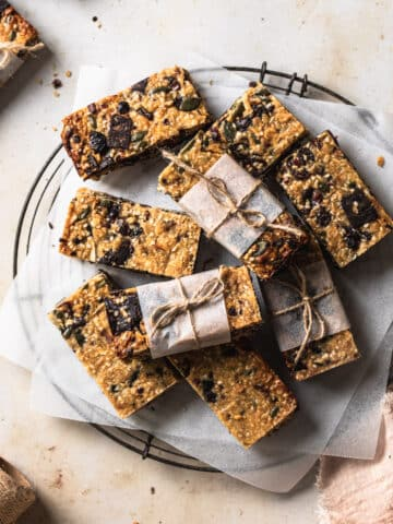 muesli slice cut into bars, stacked onto a cooling wrack.