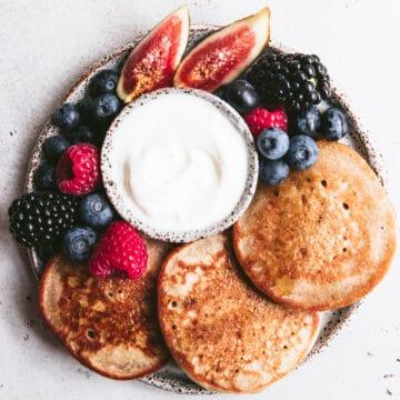 gluten free vanilla vegan buckwheat pancakes on plate with berries