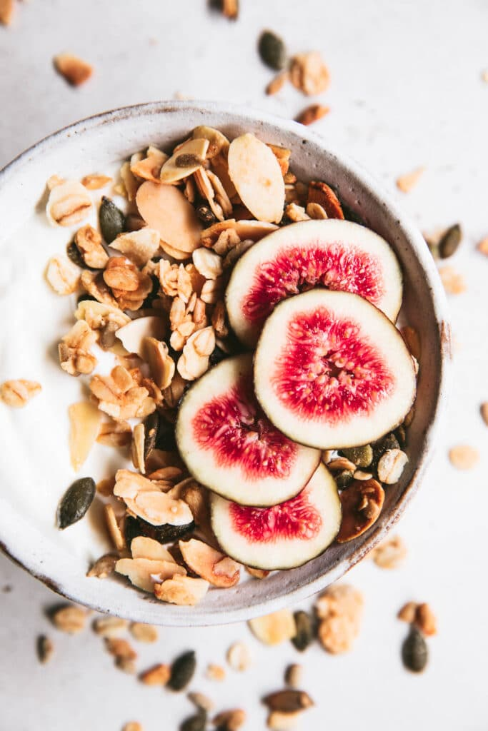 bowl of toasted almond granola topped with sliced figs