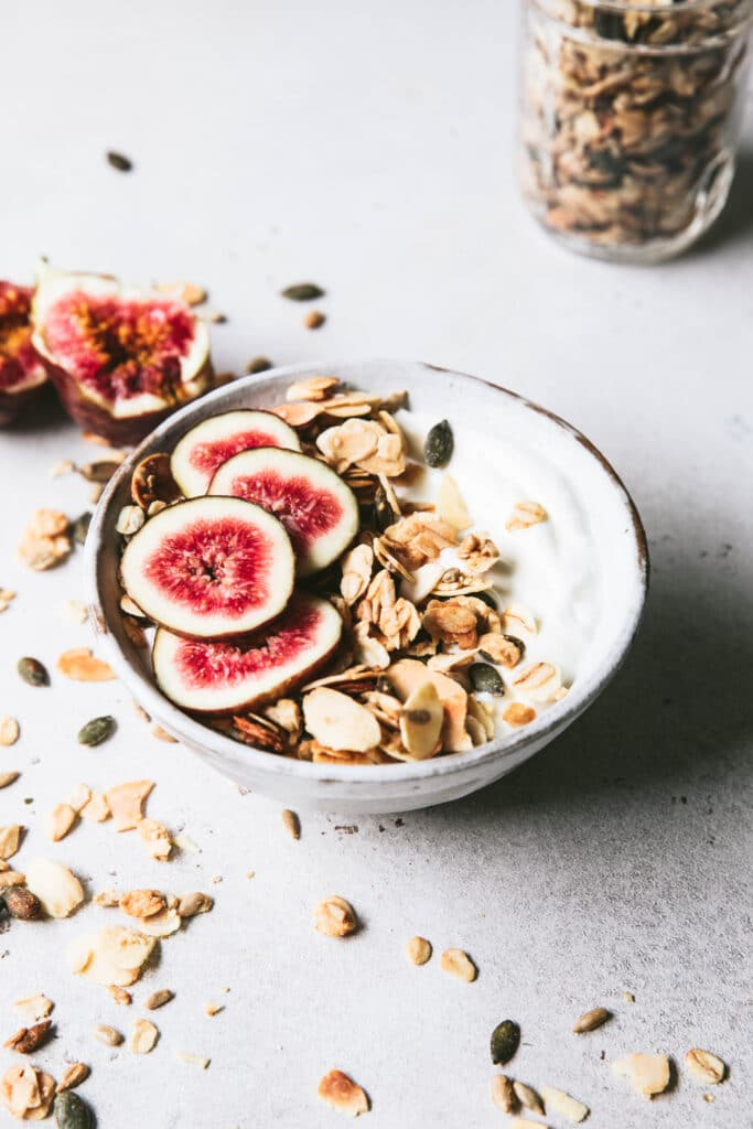 bowl of toasted almond granola topped with sliced figs, pulled apart figs in background