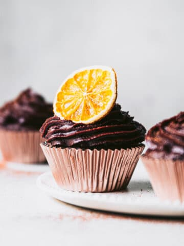 gluten free chocolate cupcakes topped with cashew cream cheese chocolate frosting and dried orange