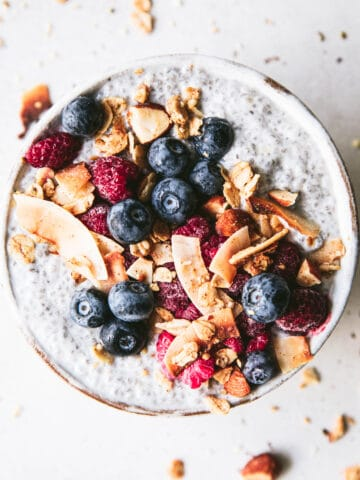 bowl of coconut chia pudding topped with berries and granola