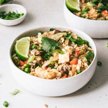 Image of two bowls of pork fried rice, coriander and lime