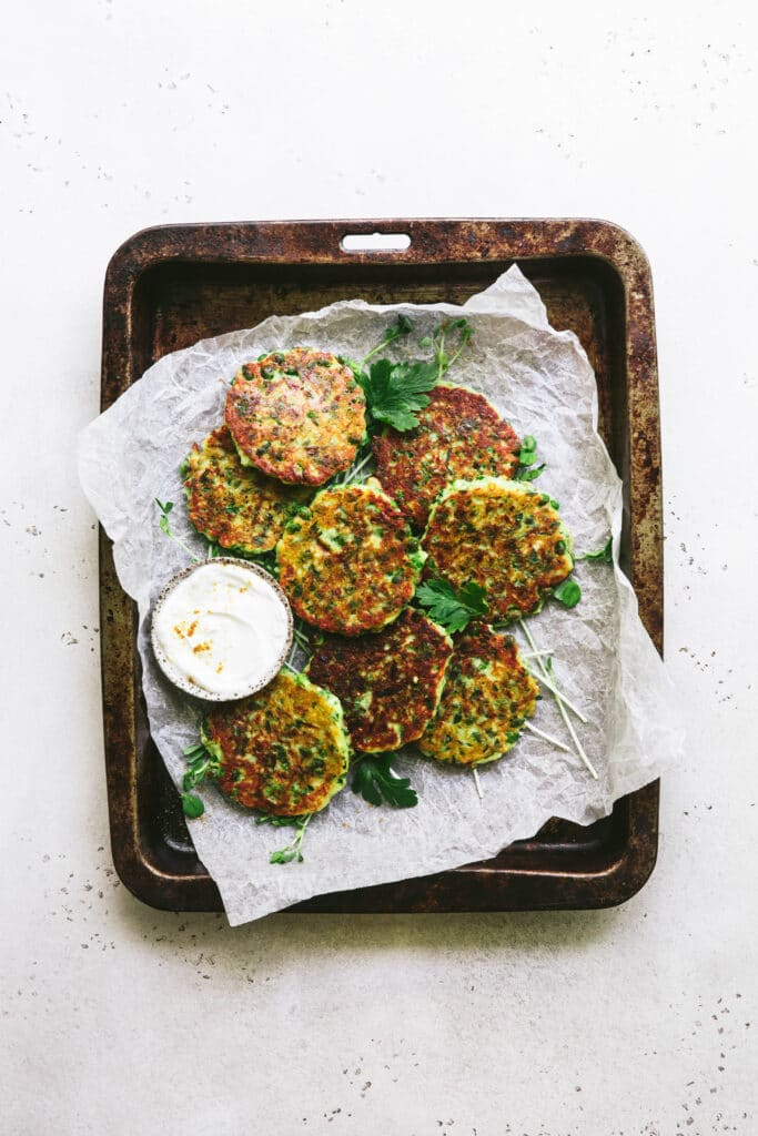 baking tray containing zucchini and pea egg free fritters with coconut yoghurt