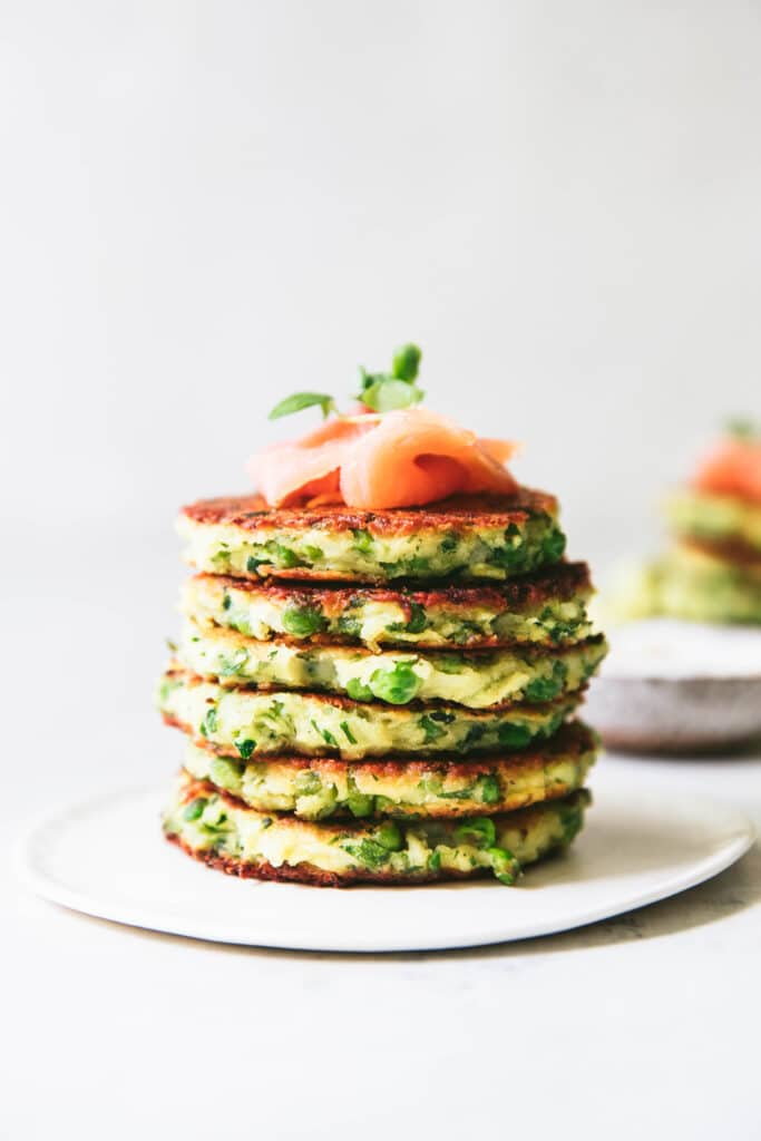 zucchini pea fritters stacked on top of each other, smoked salmon on top
