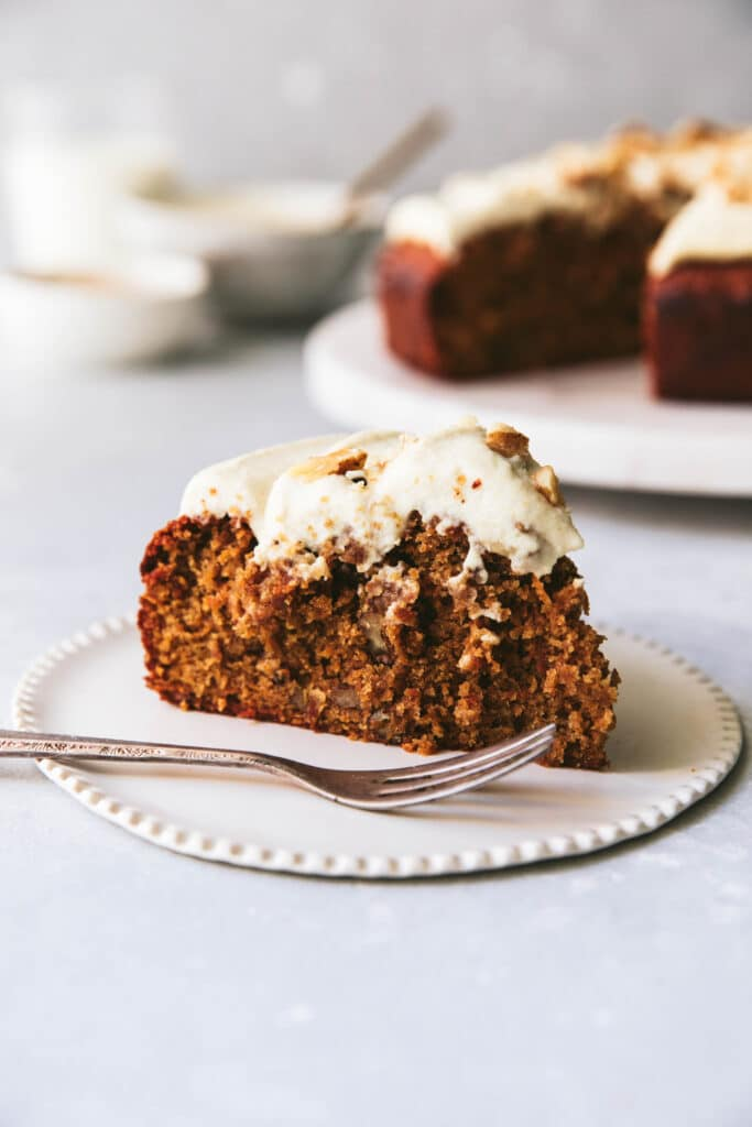 A slice of gluten free carrot cake with dairy free cream cheese frosting