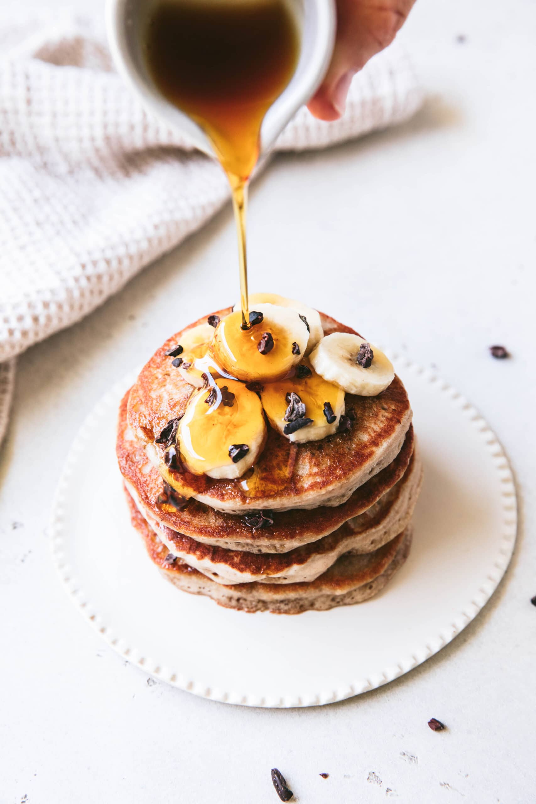 maple syrup poured over top of buckwheat pancake stack