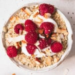 bowl of steel cut oats topped with raspberries, toasted coconut and yoghurt