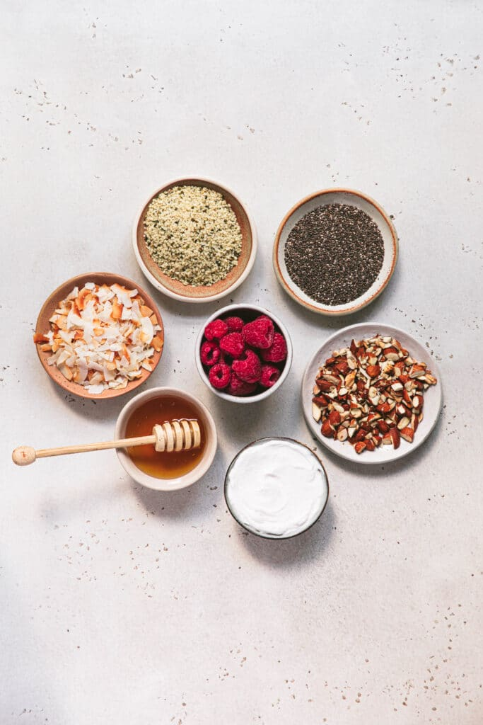 hemp seeds, chia seeds, toasted almonds, coconut flakes, coconut yoghurt, raspberries and honey