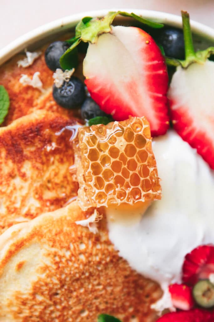 a square of honeycomb on top of pancakes