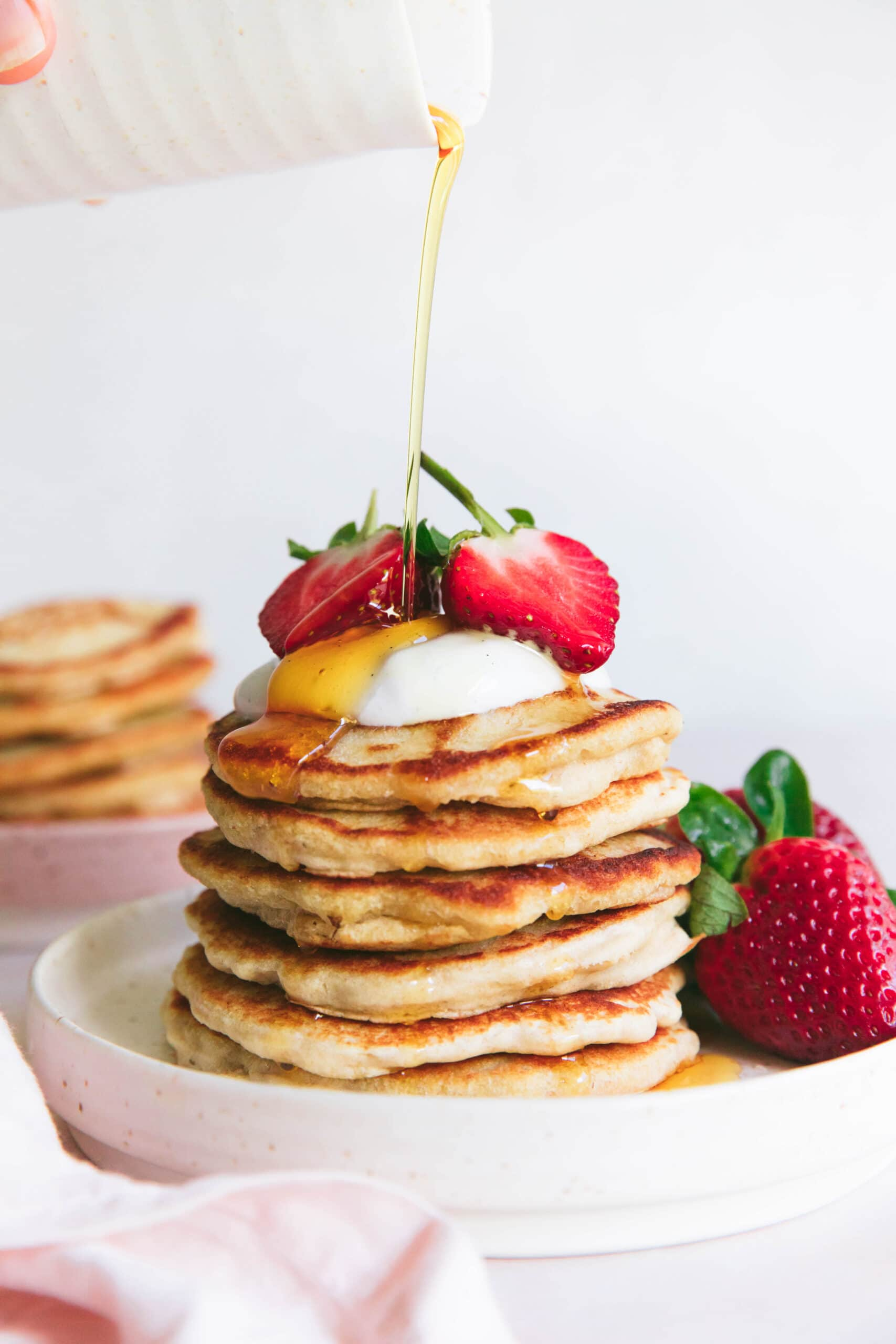stack of oat flour pancakes fizzled with maple syrup