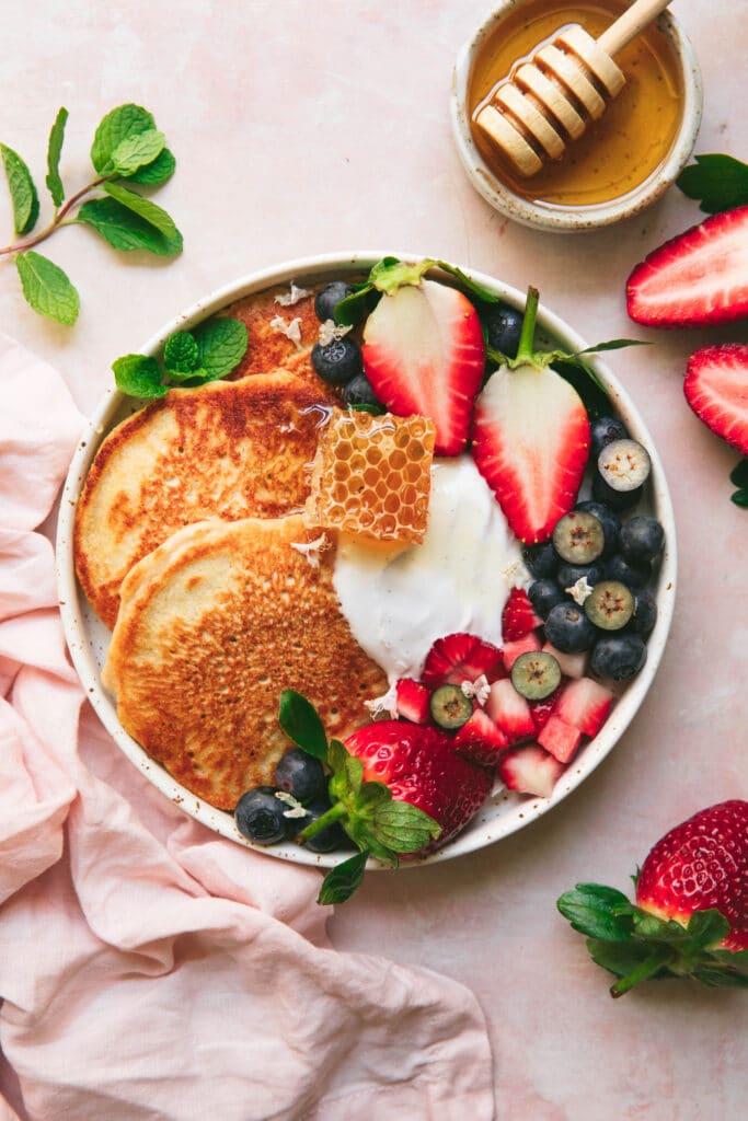 oat flour pancakes platter with coconut yoghurt, seasonal berries and honeycomb