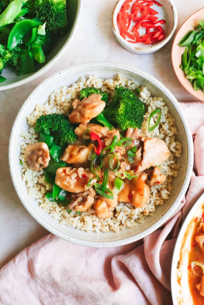 chicken teriyaki in a bowl with rice and green vegetables