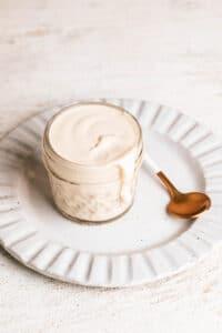 A small jar of lemon tahini dressing on a plate.