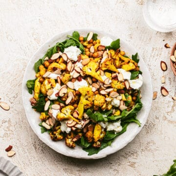 roasted cauliflower salad in ceramic bowl topped with roasted almonds