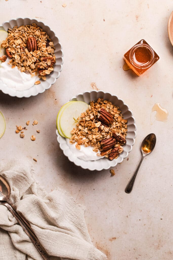 granola in a bowl with yoghurt, apple slices and honey in a jar off to the side.
