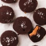 flat lay image of dark chocolate almond butter cups sprinkled with sea salt