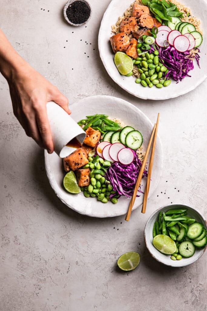pouring teriyaki style sauce into salmon poke bowl