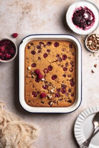 raspberry baked oats in a baking dish alongside coconut yoghurt with berry coulee
