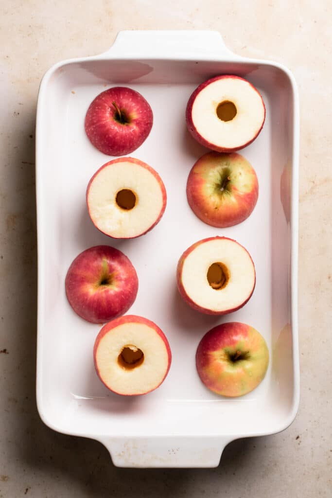 cored apples with tops removed placed into baking dish