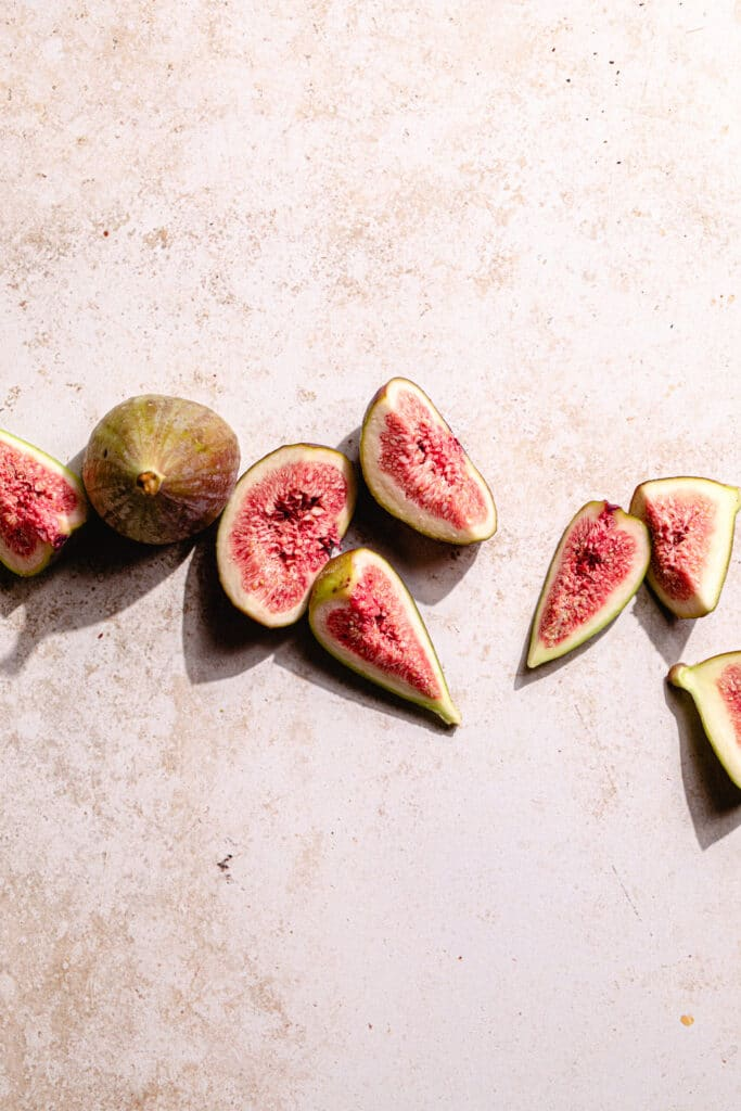 figs cut into segments on an earthy coloured backdrop