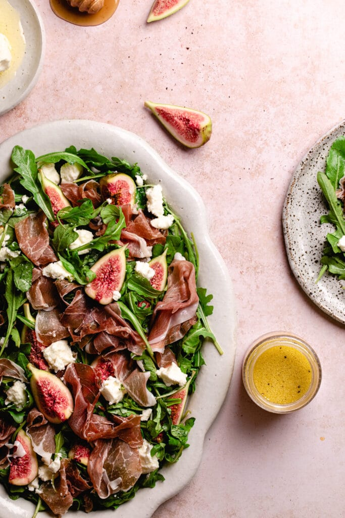 fig and goats cheese salad with prosciutto on a white platter next to a jar of apple cider vinegar dressing