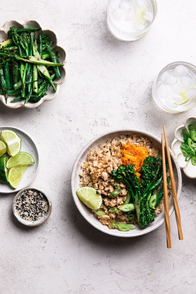 asian grain bowl with rice, ground chicken, broccolini, beans and kimchi