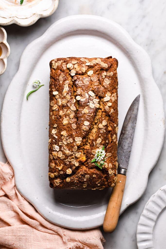 healthy oat flour banana bread on a platter with a sharp knife