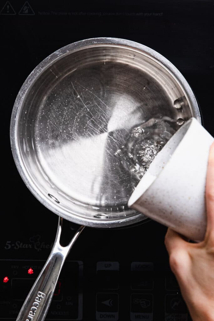 pouring water into saucepan