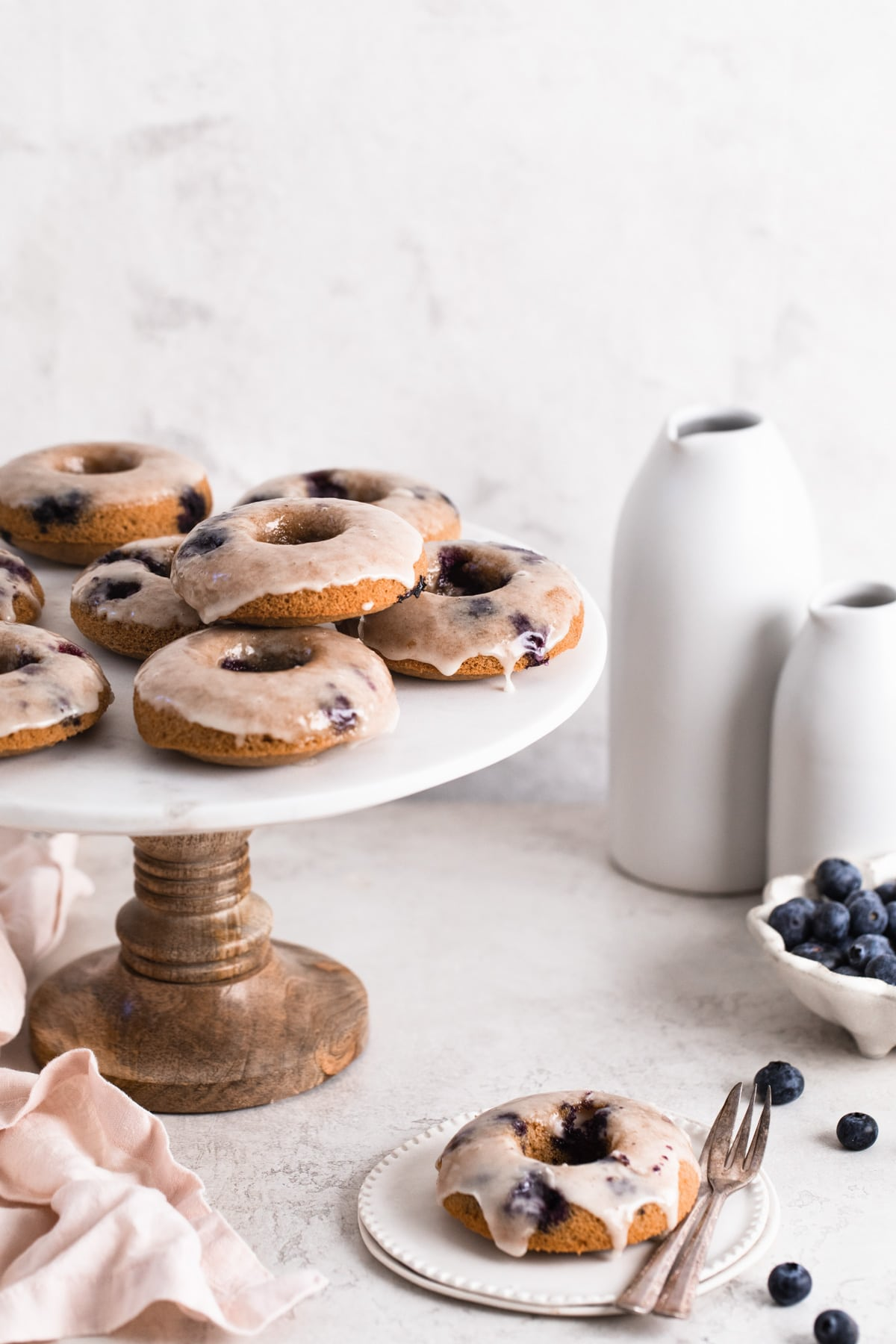 healthy baked blueberry donuts with lemon glaze on cake stand