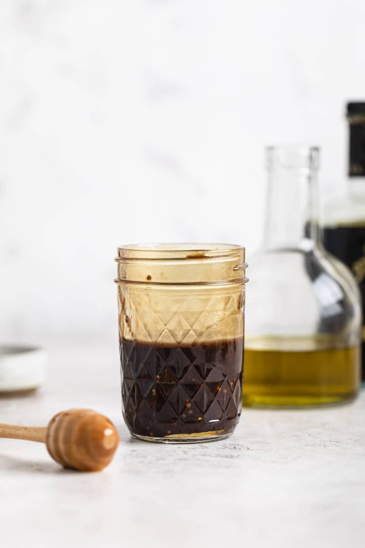 honey balsamic dressing in jar, extra virgin olive oil in glass jug in background