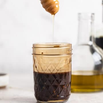 honey balsamic dressing in jar, honey being drizzled in.