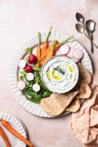 dairy free tzatziki on a platter with flat bread, baby carrots, radish and sweet peas