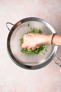 grated cucumber in a sieve sitting over the top of a glass bowl, being squeezed to extract the liquid.