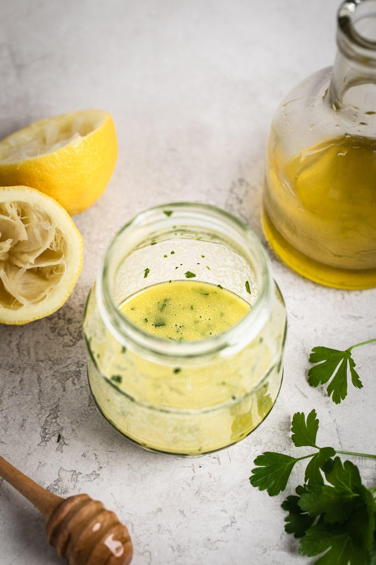 lemon herb dressing in jar with extra virgin olive oil, fresh lemon and honey