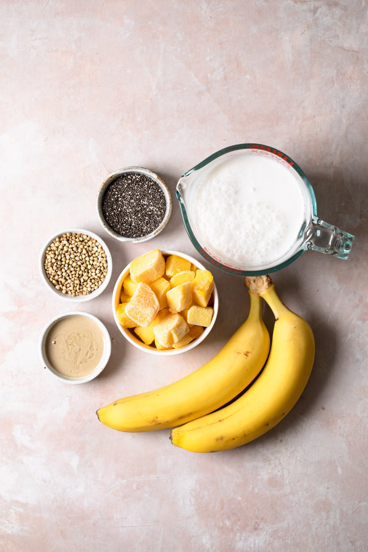 ingredients for mango banana smoothie on pink backdrop