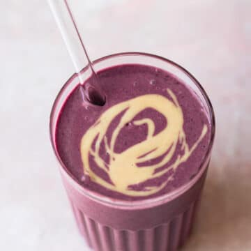 berry smoothie in glass with a swirl of tahini on top.