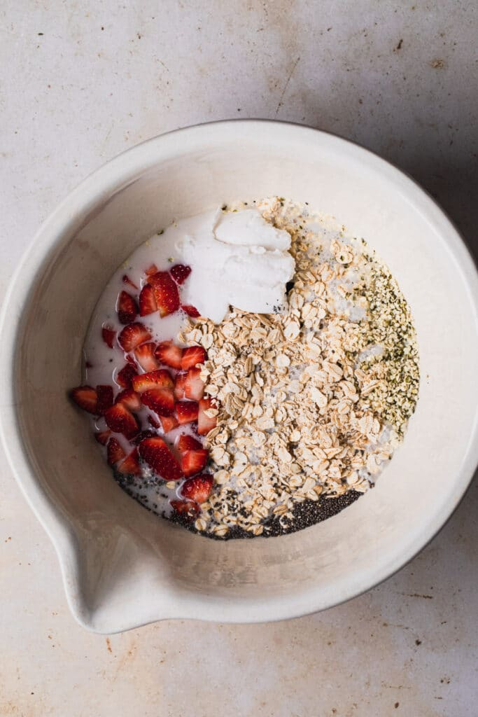 Ingredients for strawberry overnight oats in a large mixing bowl.