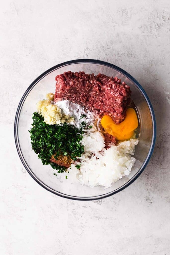 all ingredients for meatballs without breadcrumbs in a mixing bowl