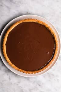 vegan dark chocolate ganache poured into a pre-baked gluten free tart shell