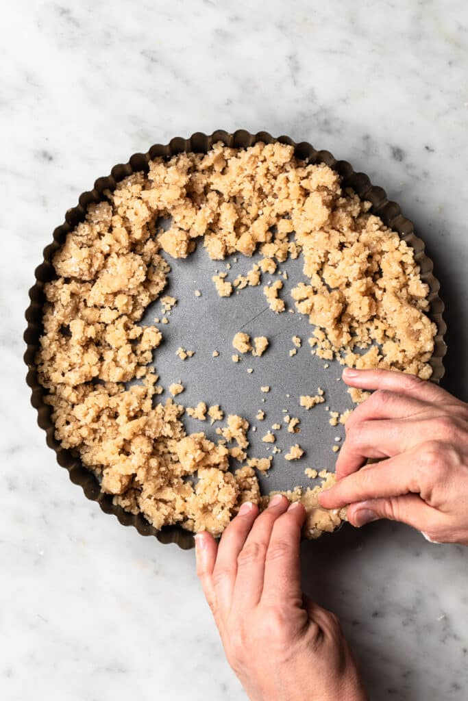Using hands to press pastry into edges of tart tin.