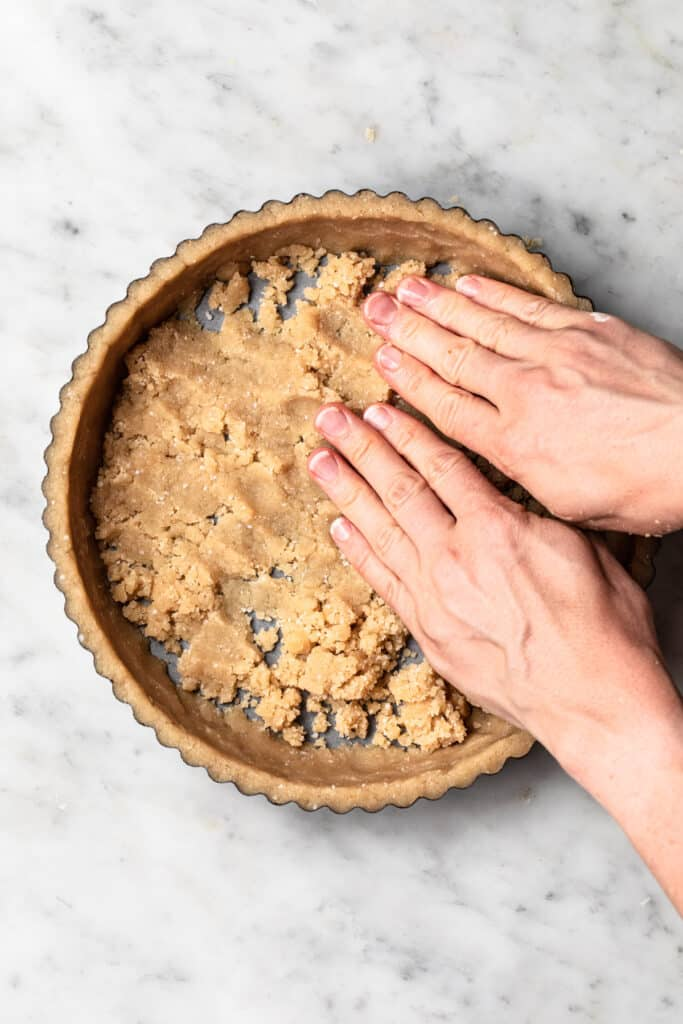 Using hands to press pastry into base of tart tin.