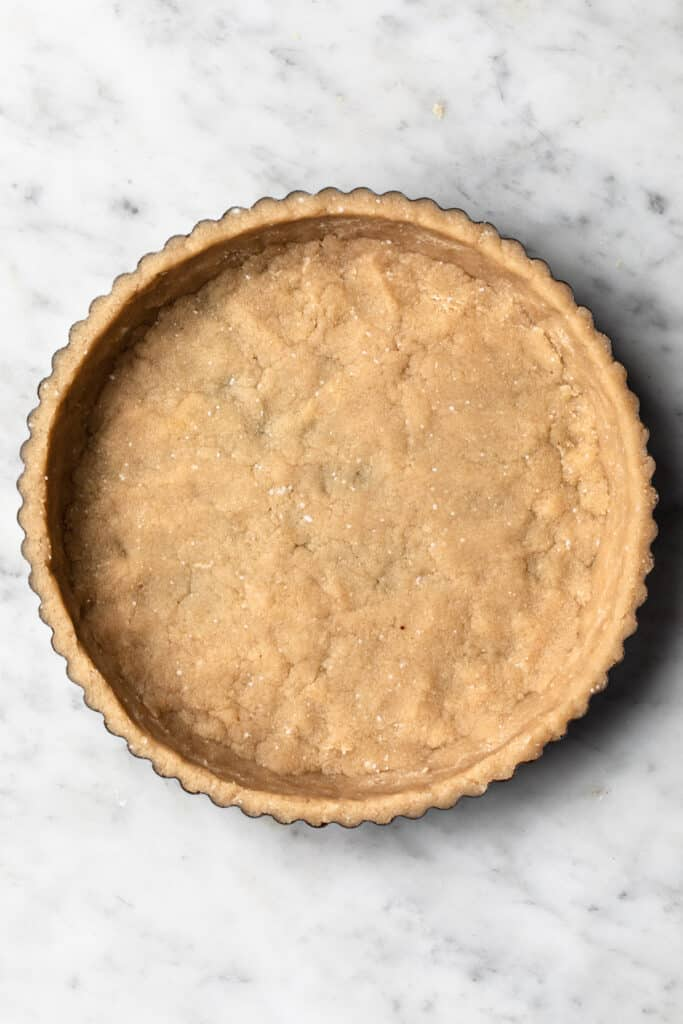 Raw pastry dough pressed out into tart tin.