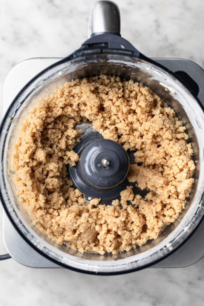 Gluten free, vegan shortcrust pastry dough in drum of food processor.