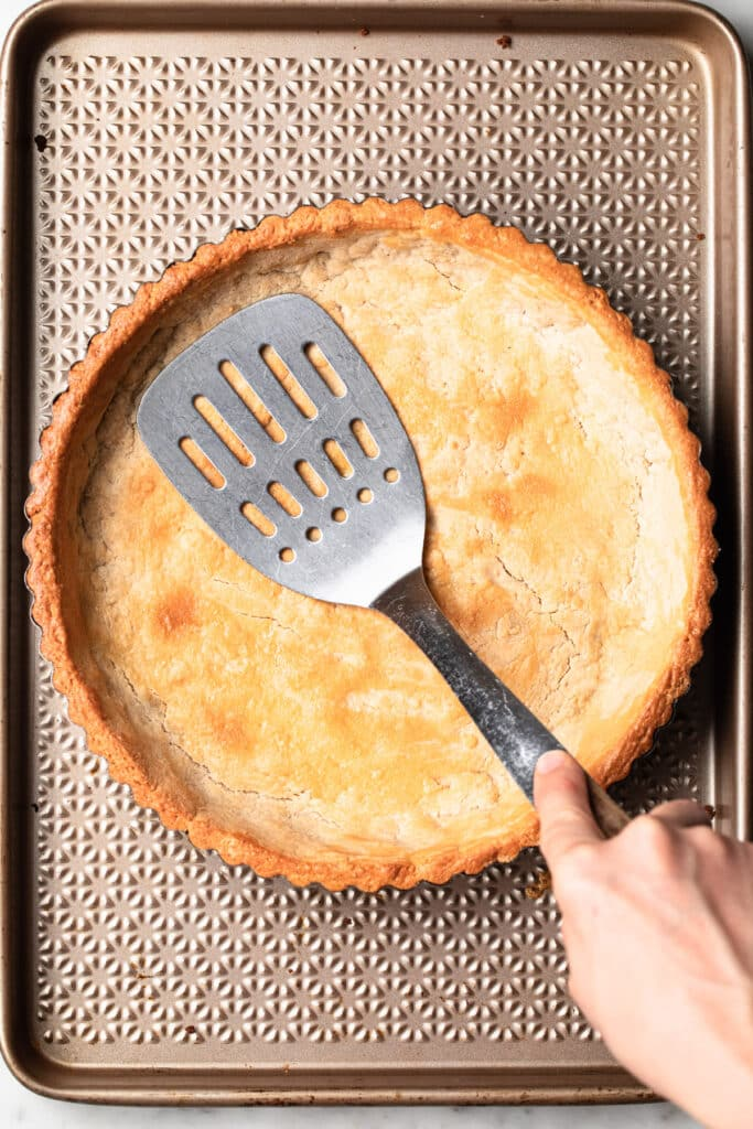 Pressing down shortcrust pastry with spatula.